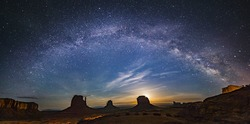 Milky way over monument valley with moon rise from background in border of Utah and Arizona, USA