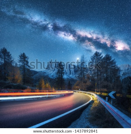 Milky Way over mountain road. Blurred car headlights on winding road in autumn. Colorful night landscape with blue starry sky with milky way, moonlight, light trails, rocks, trees and highway. Space #1437892841