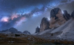 Milky Way over mountains at night in summer. Beautiful landscape with alpine mountains, blue sky with milky way and bright stars, high rocks. Tre Cime in Dolomites, Italy. Space and galaxy. Travel