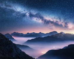 Milky Way over mountains in fog at night in summer. Landscape with foggy alpine mountain valley, purple low clouds, colorful starry sky with milky way, city illumination. Dolomites, Italy. Space