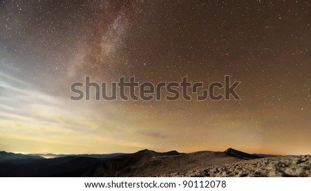 Milky Way over mountains with clouds and moon light