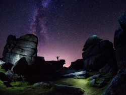 Milky Way over Rocky Landscape with Silhouette of Figure with Arms Raised, Dartmoor National Park, Devon UK