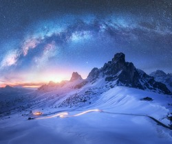 Milky Way over snowy mountains and blurred car headlights on the winding road at night in winter. Beautiful landscape with starry sky, snow covered rocks, house, roadway at sunset. Space and galaxy