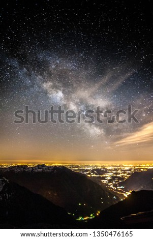 Milky way over the lights of a city in the Alps #1350476165