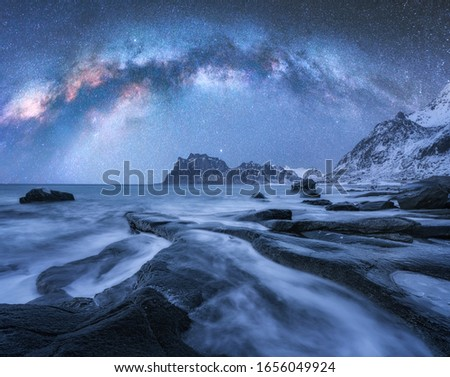 Milky Way over the snow covered mountains and rocky beach in winter at night in Lofoten Islands, Norway. Landscape with blue starry sky, water, stones, snowy rocks, bright milky way. Beautiful space