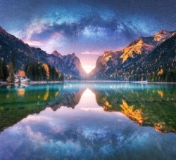 Milky Way reflected in water in mountain lake at starry night. Autumn landscape with purple sky with stars, blue fog, reflection, trees with colorful leaves, rocks in fall at sunset. Space and galaxy
