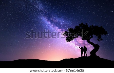 Milky Way with people under the tree on the hill. Landscape with night starry sky and silhouette of standing happy man and woman who pointing finger in starry sky. Milky way with travelers. Universe #576614635