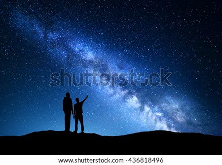 Milky Way with silhouette of a family. Father and a son who pointing finger in night starry sky on the mountain. Night landscape. Silhouette of men  on the background of beautiful universe #436818496