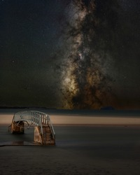 milkyway sky with the public bridge footpath submerged in water, known as the bridge to no where in dunbar, Scotland, uk.