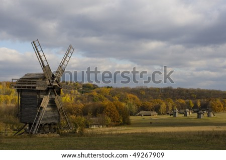 Mill against bright autumn wood in the Ukrainian park Pirogovo.
