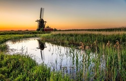 Mill by the river at dawn. River mill at dawn. Windmill at dawn. Sunrise river windmill