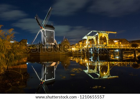 Mill de Put and the rembrandt bridge in Leiden by night and reflection in the river Rijn in LEIDEN, THE NETHERLANDS