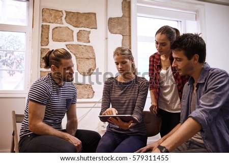 Millenial business team sitting and standing around in a semi circle all looking at the tablet in an interesting discussion