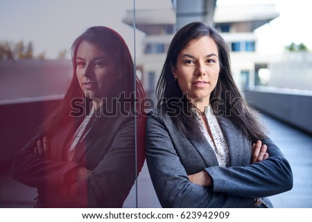 Millenial businesswoman leaning confidently on a dark glass wall with cityscape background