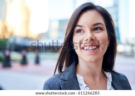 Millenial businesswoman smiling confidently with cityscape background