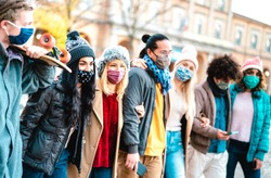 Millenial people walking and having fun together wearing face mask at old town - New normal friendship concept with multicultural friends on winter fashion clothes - Focus on left girl with black hair