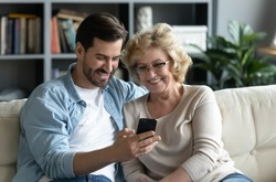 Millennial adult son demonstrates to older mother new application on smartphone sit on couch at home, helps her and teaches, shows old mom photos, share personal, having fun, modern tech usage concept