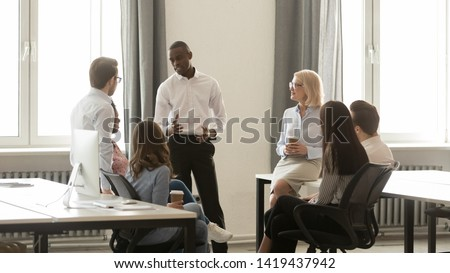 Millennial african American team leader talk explaining sharing thoughts with colleagues during casual meeting, diverse multiracial employees speak discussing business project in coworking office