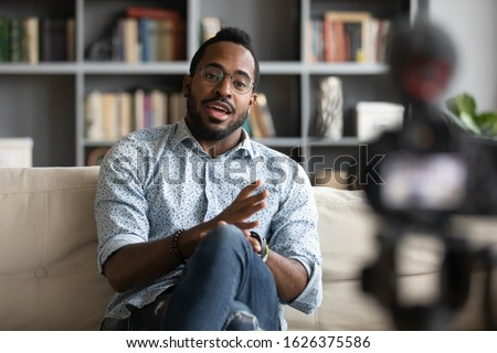 Millennial african hipster man blogger recording vlog on digital camera sit on sofa in living room, confident young guy vlogger influencer shooting social media video blog on camcorder talk at home