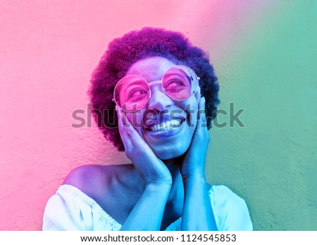 Millennial african woman smiling and wearing sunglasses - Black afro girl having fun in front of camera - Focus on face - Youth lifestyle concept - Radial blue and purple filter editing