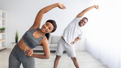 Millennial black couple doing lateral flexion exercise, working out together at home during coronavirus quarantine. Pretty young lady and her boyfriend making side bending pose, panorama