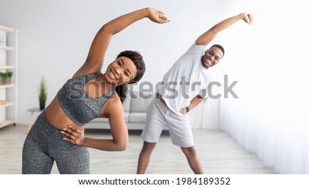 Millennial black couple doing lateral flexion exercise, working out together at home during coronavirus quarantine. Pretty young lady and her boyfriend making side bending pose, panorama Foto stock ©