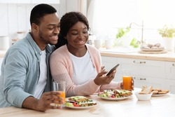 Millennial Black Man And Woman Having Breakfast And Using Smartphone In Kitchen, Happy African American Couple Browsing Internet On Mobile Phone While Eating Tasty Food At Home Together, Closeup