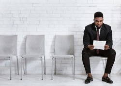 Millennial black man reading his resume while waiting for job interview at office hall, empty space. African American work candidate with CV applying for position in big company