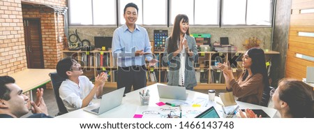 Millennial boss team leader introducing New asian woman employee to colleagues in creative office workplace. Welcoming hired newcomer member to team. first work day get clapping hands with colleagues.