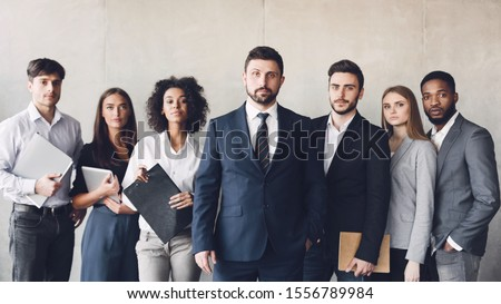 Millennial business colleagues headed with boss, posing to camera over grey wall in office