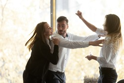 Millennial businessman calming down, setting apart two aggressive fighting female colleagues at workplace. Young women quarrelling, having conflict or misunderstanding during workday at office.