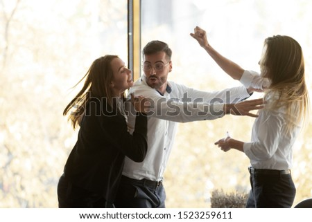 Millennial businessman calming down, setting apart two aggressive fighting female colleagues at workplace. Young women quarrelling, having conflict or misunderstanding during workday at office. Stock photo ©