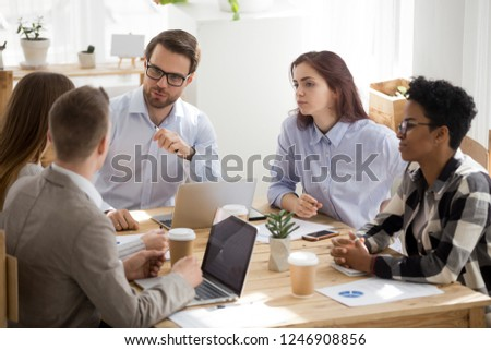 Millennial businessman in glasses head casual office meeting talking to colleague, diverse employees speak at briefing brainstorming or discussing work issues, workers cooperate listening to coworker