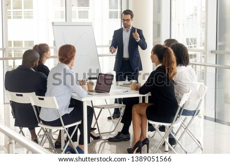 Millennial businessman in suit stand hold meeting make flip chart presentation for diverse colleagues, male coach or speaker talk present project graph on whiteboard training multiethnic work team