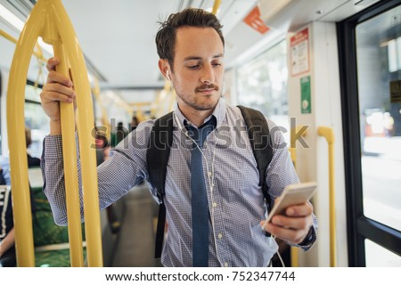 Millennial businessman is commuting on a tram in Melbourne, Victoria. He is watching something on his smart phone with headphones while standing and holding on to the rail.