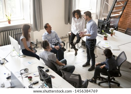 Millennial businessman speak with multiracial colleagues at informal company briefing in shared office, diverse coworkers meeting brainstorming together with male CEO, discuss business plans