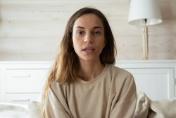 Millennial Caucasian girl sit on couch in living room look at camera having webcam conversation, young woman talk speak on video call using wireless internet connection at home, female blogger record