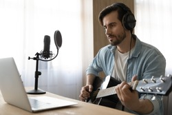 Millennial Caucasian male artist in headphones learn playing guitar watch online video lesson or tutorial on laptop at home studio. Young man singer hold use instrument, record music or song.