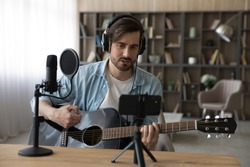 Millennial Caucasian male music tutor coach hold guitar record video tutorial on smartphone at home studio. Young man artist or singer play musical instrument, shoot new song or single on cellphone.