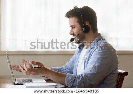 Millennial Caucasian male worker in headset talk consult client online using wireless internet on laptop, man call center agent or telemarketer in earphones speak with customer working on computer