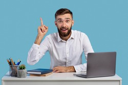 Millennial Caucasian office worker having creative idea, gesturing eureka at workplace on blue studio background. Young man finding solution to problem, sitting at his desk with laptop