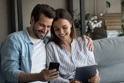 Millennial couple in love confident internet users sit on couch hold phone tablet exchange data share information between devices. Young husband wife send receive files app from cell to pad using wifi