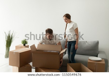 Millennial couple moving in to new flat, husband carrying cardboard boxes with personal belongings, happy young spouses settling relocating to first purchased or rented house. Living together concept #1150549676