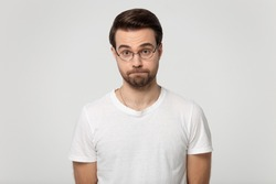 Millennial dissatisfied serious bearded man in eyeglasses squeezing lips, young surprised guy unsurely looking at someone with distrust, raising eyebrows portrait, isolated on grey studio background.
