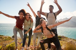 Millennial friends on a hiking trip celebrate reaching the summit and have fun posing for photos