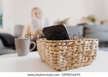 Millennial girl at home refuse using phone and reading a book. Social media addiction. Waste of time. Unplugged. Dependance concept Сток-фото ©