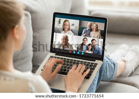 Millennial girl relax on sofa at home talk chat with diverse relatives on video call using laptop gadget, young female rest on couch have webcam conference conversation with family on computer