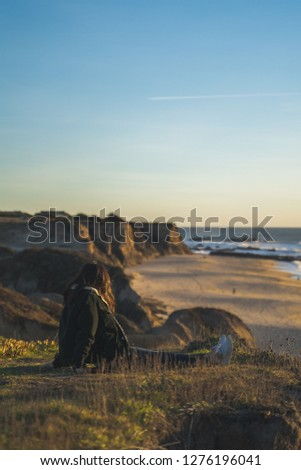 millennial girl walking around the cliffs beach and ocean of half moon bay during sunset sunrise on a beautiful contemplative introspective thought in northern california