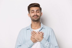 Millennial guy closed eyes put hands on chest sincerely requesting God posing isolated on white grey studio background, man believer expressing thanks or asking from heart, gratitude feelings concept