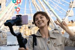 Millennial hipster teen girl blogger influencer record vlog on smart phone holf selfie stick. Travel vlogger shoot video blog instagram story,streaming on urban city street get likes and hearts emoji.